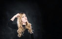 Blonde Frau, die über etwas erwägt Lizenzfreies Stockbild