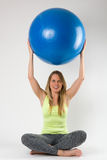 Blonde Frau, die Übungen mit einem blauen Ball tut Stockfotos