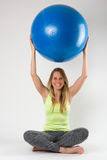 Blonde Frau, die Übungen mit einem blauen Ball tut Stockbilder