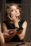 Blonde Frau, die Abendmake-up vor Spiegel tut Lizenzfreies Stockbild