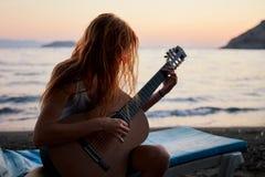 Blonde Frau, die Akustikgitarre auf dem Strand spielt Stockfoto