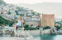 Blonde Frau, die auf alter Festungswand, Alanya-Schloss, die Türkei sitzt Stockfotos