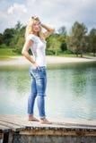 Blonde Frau, die auf Anlegestelle steht Stockfoto
