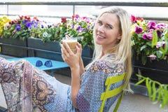 Blonde Frau, die auf Balkon mit Kaffee sitzt Lizenzfreies Stockfoto