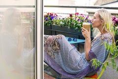 Blonde Frau, die auf Balkon mit Kaffee sitzt Lizenzfreie Stockfotos