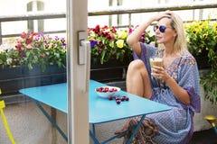 Blonde Frau, die auf Balkon mit Kaffee und Kirschen sitzt Stockfotografie
