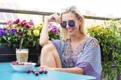 Blonde Frau, die auf Balkon mit Kaffee und Kirschen sitzt Stockbilder