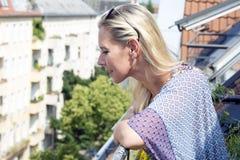 Blonde Frau, die auf Balkon steht Stockfotografie