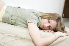 Blonde Frau, die auf Bett liegt Stockfotografie