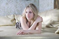 Blonde Frau, die auf Bett liegt Stockbilder