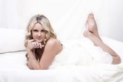 Blonde Frau, die auf Bett sich entspannt Lizenzfreie Stockfotos