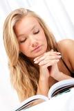 Blonde Frau, die auf Bett- und Lesebuch legt Stockfotos