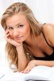 Blonde Frau, die auf Bett- und Lesebuch legt Lizenzfreies Stockfoto