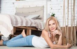 Blonde Frau, die auf Boden im Schlafzimmer liegt Lizenzfreies Stockbild
