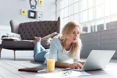Blonde Frau, die auf Boden liegt und Laptop verwendet Lizenzfreie Stockfotos