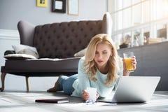 Blonde Frau, die auf Boden liegt und Saft Glas hält Lizenzfreie Stockfotografie
