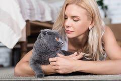 Blonde Frau, die auf Boden mit Katze liegt Stockfoto