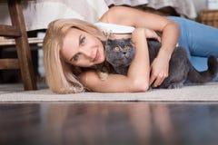 Blonde Frau, die auf Boden mit Katze liegt Lizenzfreie Stockfotografie
