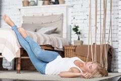 Blonde Frau, die auf Boden nahe Bett liegt Stockfotografie
