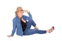 Blonde Frau, die auf Boden sitzt Stockfoto
