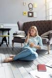Blonde Frau, die auf Boden sitzt und pro Telefon spricht Stockfotografie