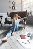 Blonde Frau, die auf Boden sitzt und pro Telefon spricht Lizenzfreie Stockbilder