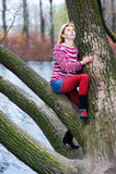 Blonde Frau, die auf dem Baum sitzt Stockbild