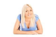 Blonde Frau, die auf dem Boden liegt und Kamera betrachtet Lizenzfreie Stockbilder