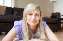 Blonde Frau, die auf dem Fußboden liegt Stockbilder