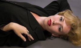 Blonde Frau, die auf dem Fußboden liegt Stockfotografie