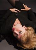 Blonde Frau, die auf dem Fußboden liegt Stockbild