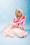 Blonde Frau, die auf dem Fußboden sitzt Lizenzfreies Stockbild