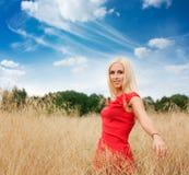 Blonde Frau, die auf dem Gebiet aufwirft Stockbild