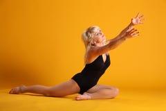 Blonde Frau, die auf dem Gelb heraus erreicht sitzt Lizenzfreie Stockfotos