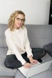 Blonde Frau, die auf dem Sofa mit Laptop verwendet Stockfotos