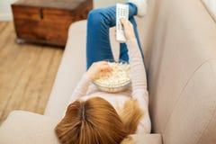 Blonde Frau, die auf dem Sofa mit Popcorn sich entspannt Stockbild