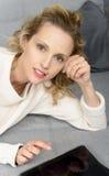 Blonde Frau, die auf dem Sofa mit Tablet-Computer sich entspannt Stockbilder