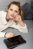 Blonde Frau, die auf dem Sofa mit Tablet-Computer sich entspannt Stockbild