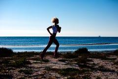 Blonde Frau, die auf dem Strand rüttelt Lizenzfreie Stockbilder