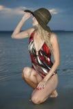 Blonde Frau, die auf dem Strand sitzt Stockfoto