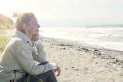 Blonde Frau, die auf dem Strand sitzt Lizenzfreie Stockfotos