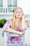 Blonde Frau, die auf dem Stuhl sitzt Lizenzfreie Stockfotos
