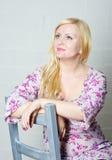 Blonde Frau, die auf dem Stuhl sitzt Stockfotos