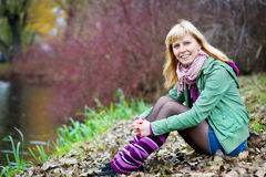 Blonde Frau, die auf der Flussquerneigung sitzt Lizenzfreie Stockfotografie