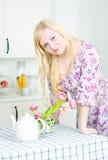 Blonde Frau, die auf der Tabelle sich lehnt Stockfotografie