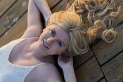 Blonde Frau, die auf die Plattform legt Lizenzfreies Stockbild