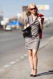 Blonde Frau, die auf die Straße geht Stockfotografie