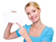 Blonde Frau, die auf die unbelegte weiße Karte zeigt Lizenzfreie Stockbilder