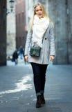 Blonde Frau, die auf eine Straße geht Stockfotos