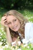 Blonde Frau, die auf einem Gebiet legt Lizenzfreies Stockfoto